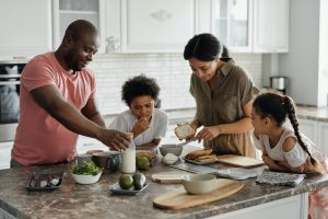 Family uses household goods products to cook a meal together in the kitchen.