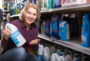 A woman shops for laundry detergent in the supermarket.
