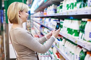Woman using mobile phone to photograph with smartphone label of dairy products